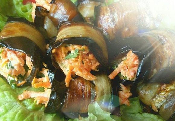 Eggplant rolls lie on a platter in salad leaves